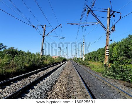 Double-track electrified railway on a clear sunny day.