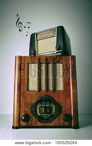 Two old retro revival radios on top of another with music notes
