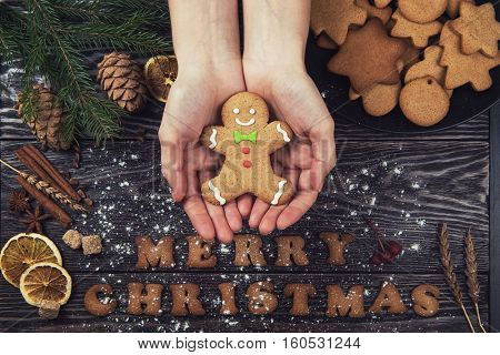 Woman hands keep ginger cookies for new years and christmas on wooden background.