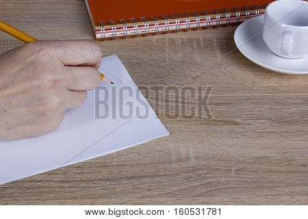 Hand of man with a pencil behind his desk