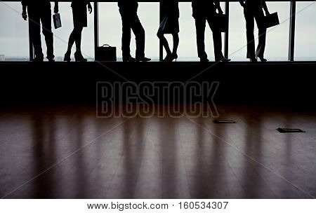 Legs of business people against window in dark shapes