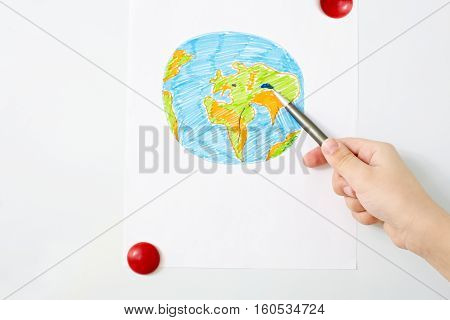 Hand of a child pointing at a painted Earth