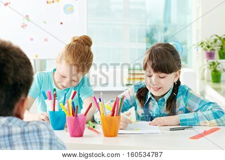 Two little girls drawing at preschool lesson