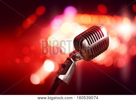 Close up of microphone in concert hall with blurred lights at background