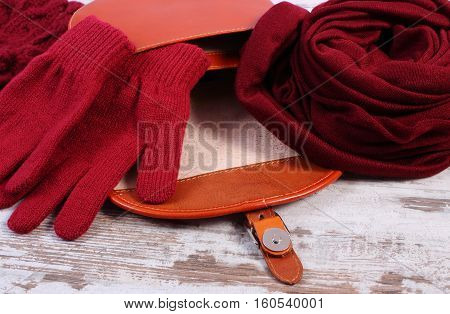 Woolen Gloves And Shawl With Open Leather Handbag For Woman On Old Wooden Background