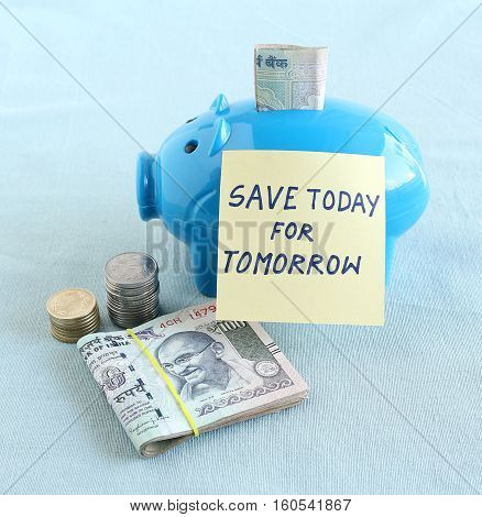 Financial concept of the need for saving money today for tomorrow indicated through a handwritten text on a note posted on a piggy bank.