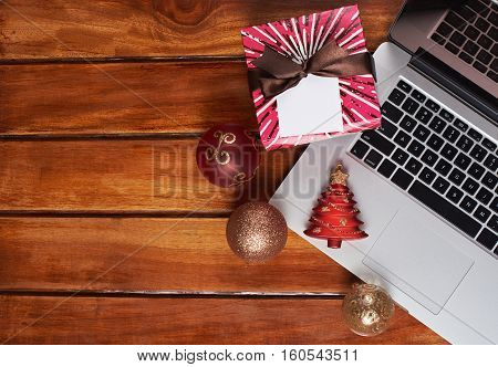 Christmas toys with laptop on wooden table. Empty copy space with christmas decoration