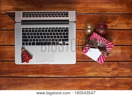 Modern laptop on wooden table with christmas toys and gift box ribbon