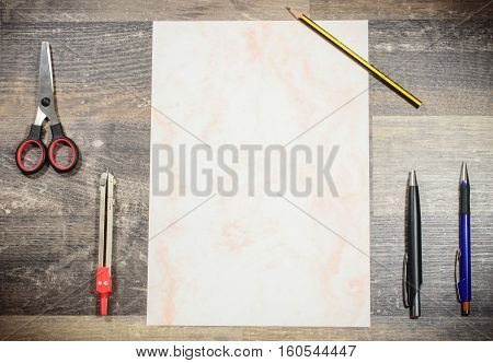 On a subsoil of wood are clear arranged a patterned sheet of paper 2 ballpoint pens a pencil a circle and scissors