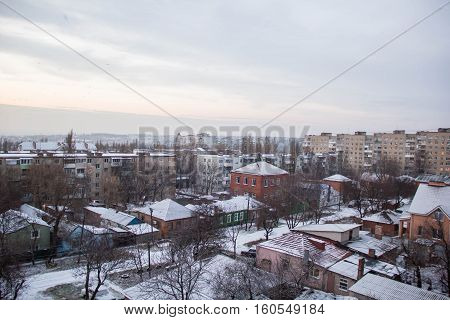 Winter view from the window of an apartment building with modern and old houses