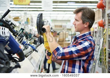 Man Shopping For Angle Grinder In Hardware Store