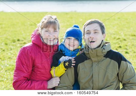 Family portrait of three smiling people in sunny fall park