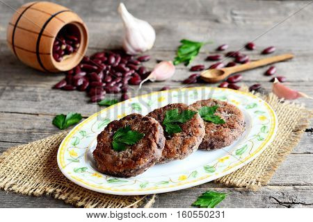 Burgers made from boiled and mashed red beans on a plate. Scattered uncooked red beans, garlic, fresh parsley, small spoon and decorative barrel on old wooden background. Vegetarian burgers. Closeup