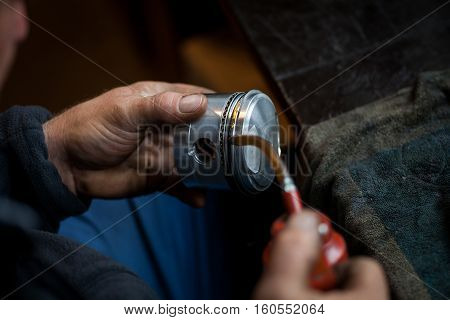 Color image of a mechanic oiling a motorcycle piston.