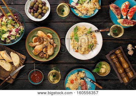 Italian risotto with roasted chicken legs snacks and wine on dark wooden table. Italian food table top view