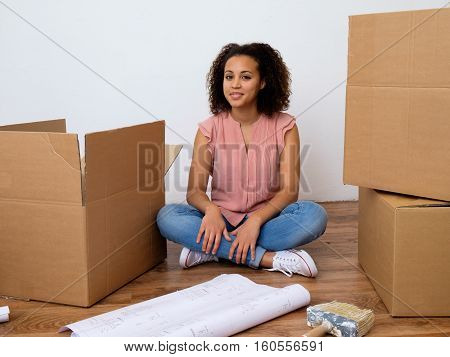 Happy woman surrounded by large boxes ready for home relocation