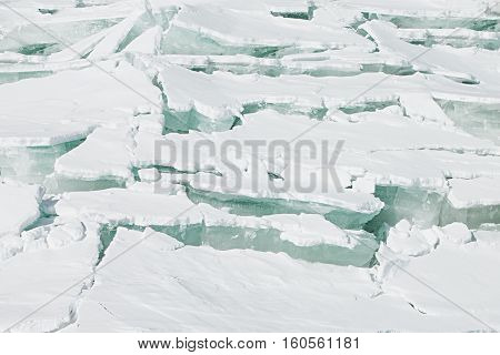 Ice background of huge blocks of aqua ice from fractured floes. Winter backdrop.