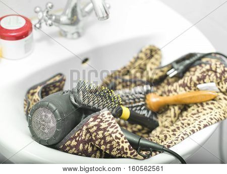 A hairdryer laid on the towel in a sink a faucet in the blurred background
