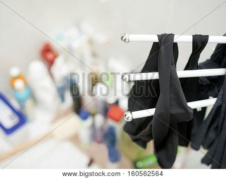 Underwear and socks drying on a clothes rack in a bathroom a bunch of cosmetics in the blurred background. Shallow depth of field