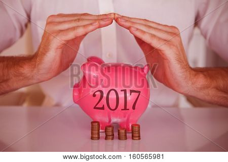 Casual businessman sheltering piggy bank and coins against digital image of new year 2017