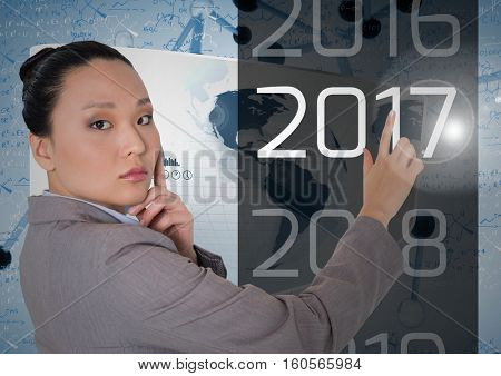 Portrait of thoughtful business woman touching 2017 in 3D digitally generated background