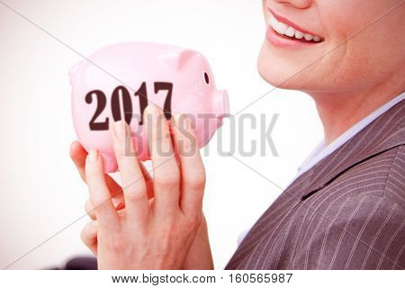 Cheerful businesswoman holding a piggybank against digital image of new year 2017