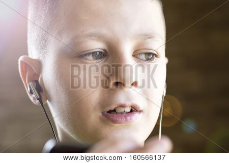Young Boy Using A Smart Phone To Listening Music With Headphones