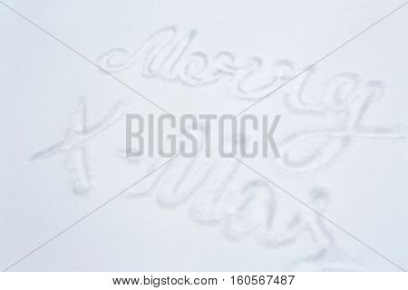 winter holidays and christmas concept - merry x-mas words on snow surface