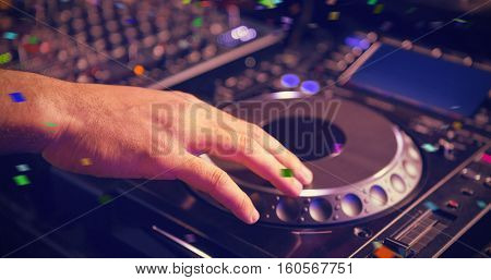 Male DJ playing music against flying colours