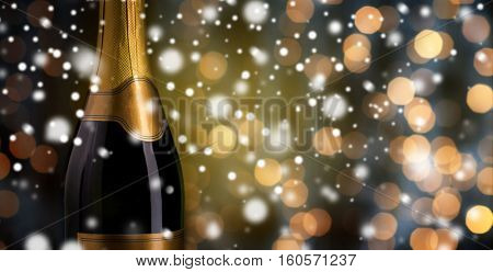 drink, alcohol, christmas, new year and winter holidays concept - close up of bottle of champagne with blank golden label over dark background with snow and lights
