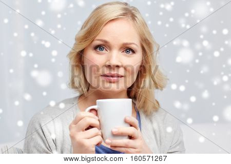 people, drinks and leisure concept - woman with cup of tea or coffee at home over snow