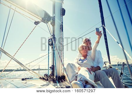 sailing, technology, tourism, travel and people concept - happy senior couple with smartphone taking selfie on sail boat or yacht deck floating in sea