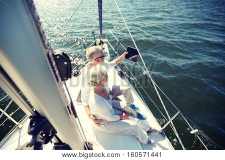 sailing, technology, tourism, travel and people concept - happy senior couple with tablet pc computer on sail boat or yacht deck floating in sea