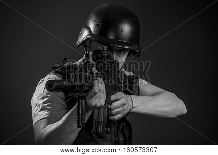 Targeting, paintball sport player wearing protective helmet aiming pistol ,black armor and machine gun