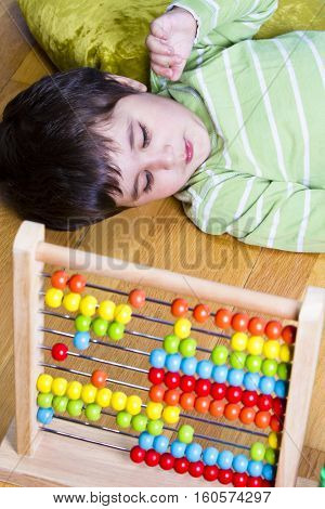 Funny little boy playing with abacus, studio shot