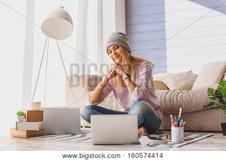 Cool young girl is entertaining at home with laptop. She is sitting on floor and smiling. Boxes near her