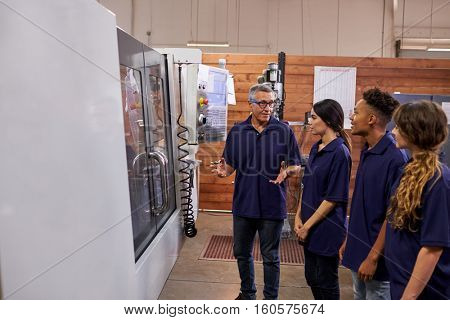 Engineer Training Apprentices On CNC Machine