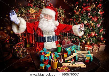 Workshop of Santa Claus. Portrait of Santa Claus making Christmas gifts at home near beautiful Christmas tree and a fireplace.