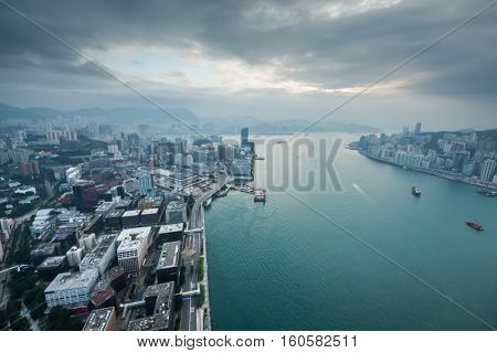 Modern skyscrapers in fog on waterside and cloudy sky in Hong Kong, China, view from New World Center