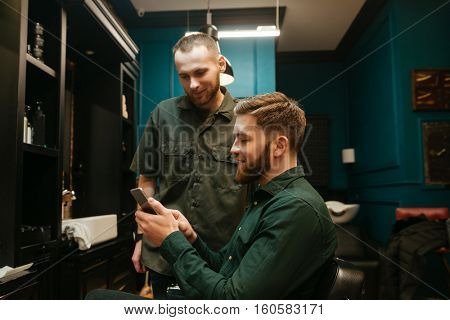 Happy young hipster man getting haircut by hairdresser while sitting in chair. Holding phone.