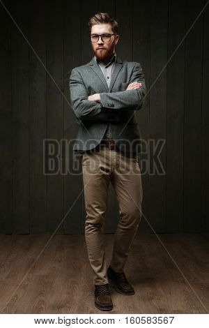 Full length portrait of a serious casual businessman standing with arms folded isolated on the black wooden background