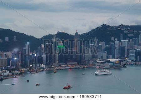Skyscraper Central Plaza on sea shore in business area, ships at cloudy evening in Hong Kong, China, view from Harbourfront center