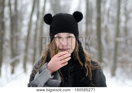 A blond long-haired girl in a funny hat with panda ears is drinking coffee on a winter day outside