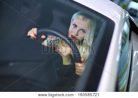 Beautiful woman sits at wheel in modern car in parking, top view