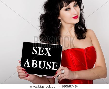 sex abuse written on virtual screen. technology, internet and networking concept. sexy woman in a red corset holding pc tablet.