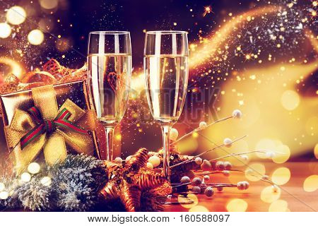 Christmas and New Year Celebration. Two Champagne Glasses and Gifts over Golden Blinking Holiday Background. Christmas party, Winter Holiday party, Xmas decoration.