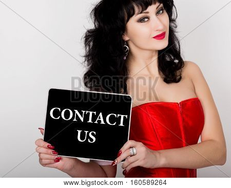 contact us written on virtual screen. technology, internet and networking concept. sexy woman in a red corset holding pc tablet.