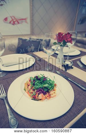 Warm appetizer made of shrimps and vegetables on restaurant table , toned image
