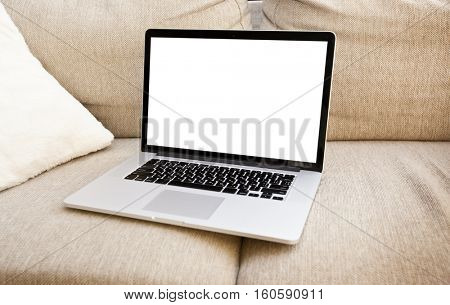 The modern laptop is lying on the sofa