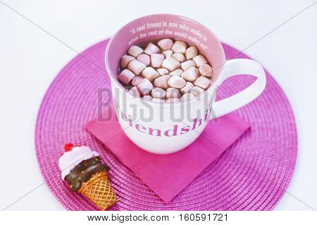Cup of hot chocolate with sweet marshmallows on a pink placement with ice cream cone magnet. A friendship quote painted on the cup. Natural light. Isolated on white.